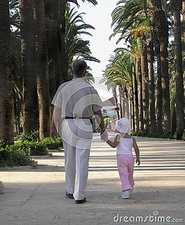 Menina que anda em um parque com seu avô