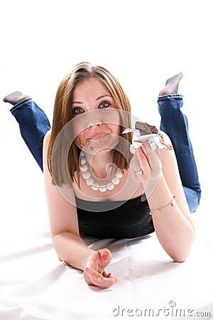 Menina que encontra-se no assoalho e que come o chocolate