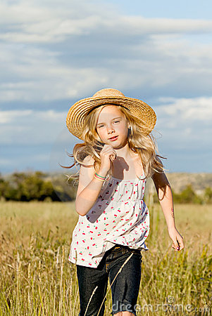 Menina que funciona através da grama longa