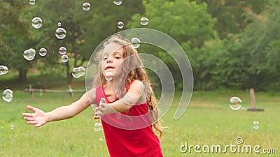 Menina que joga bolhas de sabão da captura no jardim Movimento lento Fim acima video estoque