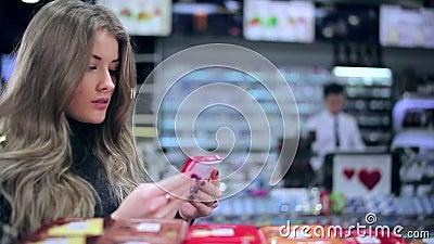 Menina que lê a composição da barra de chocolate video estoque