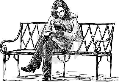 Menina que lê o livro em um banco