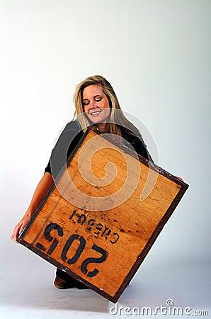 Menina que levanta uma caixa pesada
