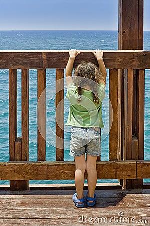 Menina que olha fixamente no mar