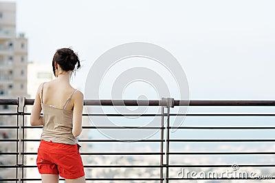 Menina que olha na cidade