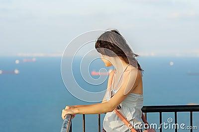 Menina que olha no mar