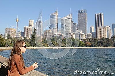Menina que olha à skyline de sydney