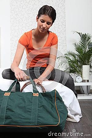 Menina que prepara o saco do curso