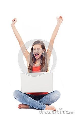 Menina que senta-se com portátil, braços levantados