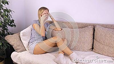 A menina que senta-se no sofá fricciona sua cara com suas mãos filme