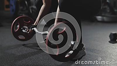 Menina que toma o barbell para treinar no gym escuro no movimento lento filme