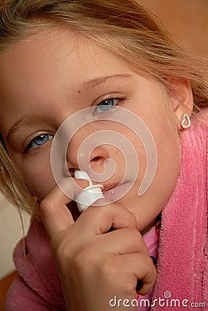 Menina que usa o pulverizador nasal