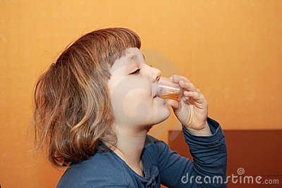 A menina toma a medicina. Bebe o xarope