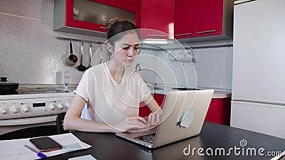 Menina trabalhando com laptop na cozinha em casa vídeos de arquivo