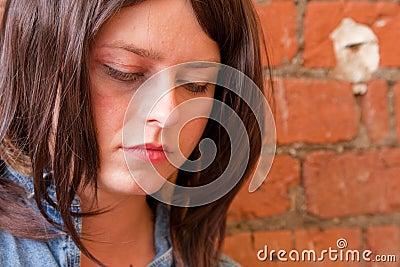 Menina triguenha deprimida que olha fixamente para baixo