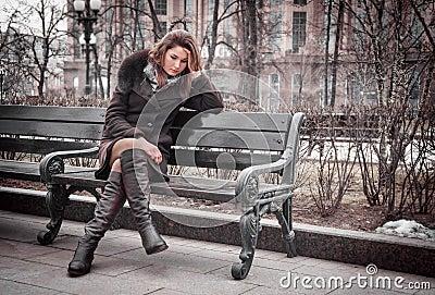 A menina triste senta-se no banco