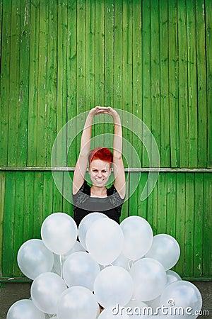 Menina vermelha do cabelo com balões de prata
