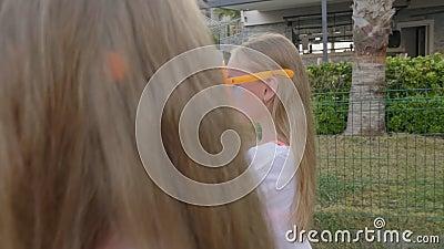 Meninas bonitas com óculos de sol engraçados andando na rua video estoque