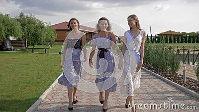 Meninas bonitas elegantes nos vestidos e nos saltos altos que andam na passagem no parque filme
