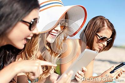 Meninas com o PC da tabuleta na praia