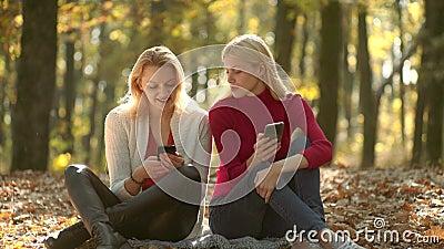 Meninas com telefone Blogger novo, conceito do blogue Duas meninas que usam o telefone esperto Aprendizagem em linha, conceito do video estoque