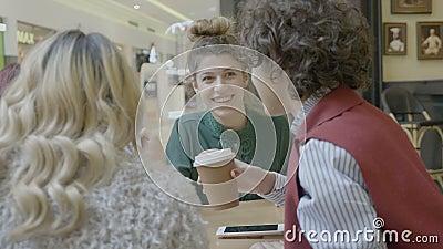 Meninas do estudante dos colegas que bebem o café que fala e que olha artigos da forma em linha no smartphone após a compra na al vídeos de arquivo