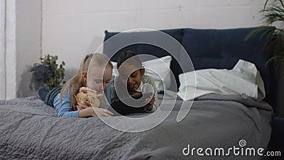 Meninas do preteen da diversidade que jogam o PC da tabuleta em casa video estoque