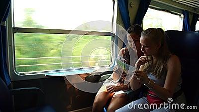 Meninas olham para folheto e falam sobre passagens de paisagens no trem filme