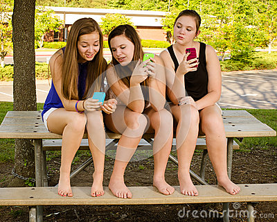 Meninas Pre-adolescentes que texting ao pendurar para fora na parte dianteira
