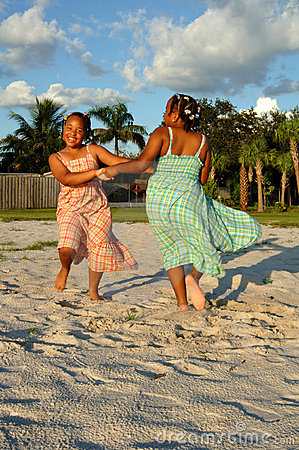 Meninas que dançam na areia na praia