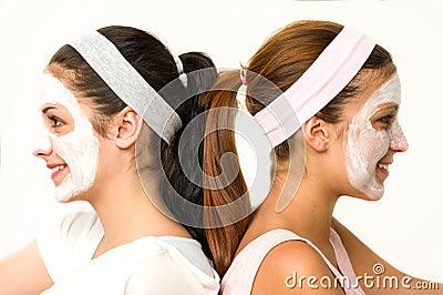 Meninas que sentam a máscara facial vestindo lado a lado