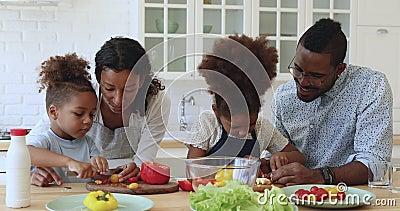 Menino africano ajudando pais a cortar salada vegetal