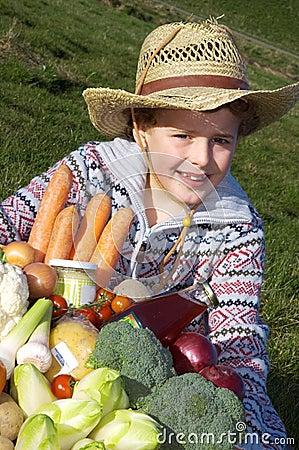 Menino com vegetais da colheita