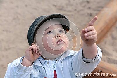 Menino curioso, apontando com dedo para cima
