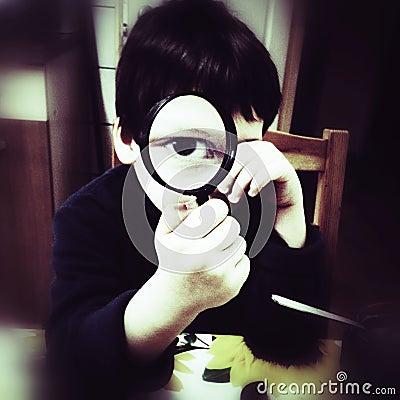 Menino curioso com magnifier