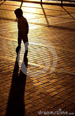 Menino da sombra do por do sol