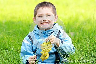 Menino de sorriso Toothy com uvas