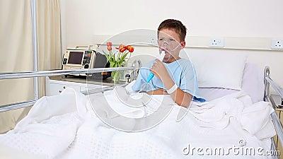 Menino doente pequeno que senta-se na cama com máscara de oxigênio video estoque