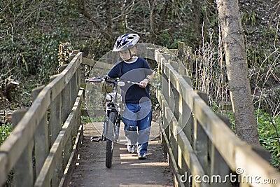 Menino dos anos de idade seis que empurra uma bicicleta