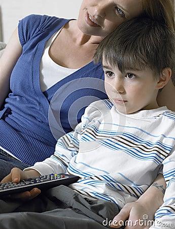 Menino e mãe que olham a tevê em casa