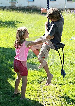Menino e menina molhados em um balanço