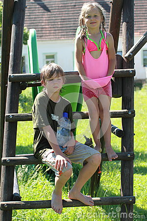 Menino e menina molhados na corrediça