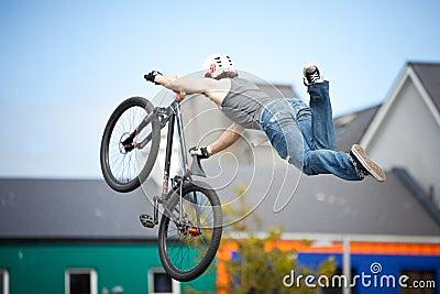 Menino em um salto da bicicleta do bmx/montanha Imagem Editorial