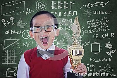 Menino entusiasmado do estudante que guarda o troféu na classe