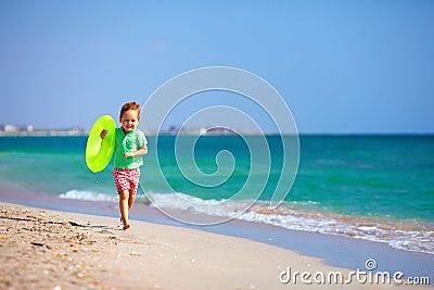 Menino feliz que corre a praia, expressando o prazer