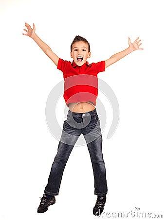 Menino feliz que salta com mãos levantadas acima