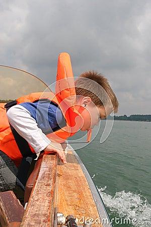 Menino na veste de vida que inclina-se sobre trilhos do barco