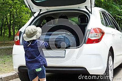 Menino pequeno que carrega sua mala de viagem