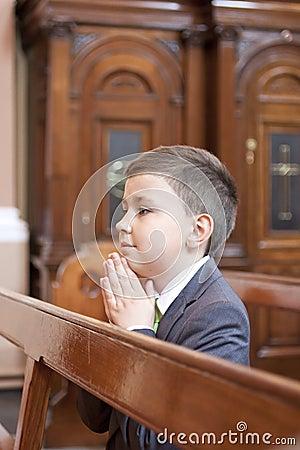 Menino que ajoelha-se e que praying na igreja.