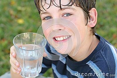 Menino que bebe um vidro da água